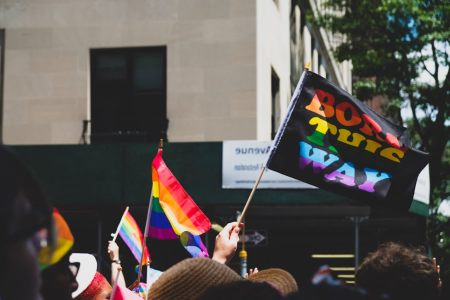 """Tops of heads visible at a Pride march with a flag that says: """"Born this way"""""""